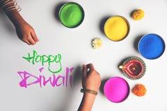 使用五颜六色的Rangoli的愉快的屠妖节贺卡在碗、diya或黏土灯和愉快的diwali文字与花 免版税图库摄影