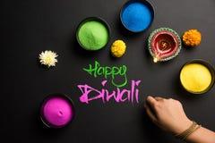 使用五颜六色的Rangoli的愉快的屠妖节贺卡在碗、diya或黏土灯和愉快的diwali文字与花 库存图片