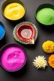 使用五颜六色的Rangoli的愉快的屠妖节贺卡在碗、diya或黏土灯和愉快的diwali文字与花 免版税库存照片