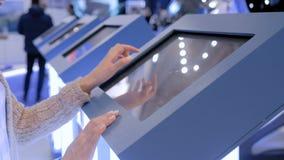 使用交互式触摸屏幕显示的妇女在技术陈列 股票录像