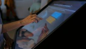使用交互式触摸屏幕显示的妇女在现代博物馆