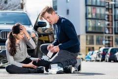 使用从他的急救工具的年轻司机不育的绷带到h 图库摄影