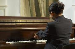 使用从返回的钢琴老师 库存照片