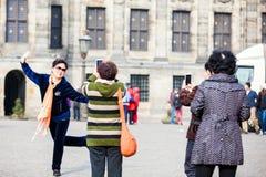使用他们的手机的亚裔游人拍照片在水坝在阿姆斯特丹摆正 库存图片