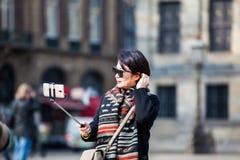 使用他们的手机的亚裔游人拍照片在水坝在阿姆斯特丹摆正 库存照片
