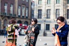 使用他们的手机的亚裔游人拍照片在水坝在阿姆斯特丹摆正 免版税库存照片