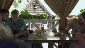 使用他们的电话的小组四青年人在咖啡馆 股票录像