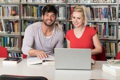 使用他们的膝上型计算机的年轻学生在图书馆 图库摄影