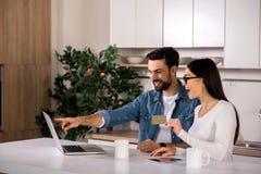 使用他们的膝上型计算机的快乐的yougn夫妇财政规划的 免版税库存照片