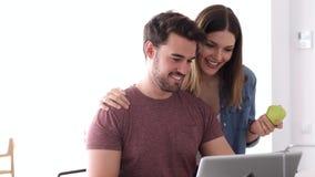 使用他们的膝上型计算机的美好的可爱的年轻夫妇和在家谈话在厨房里 股票视频