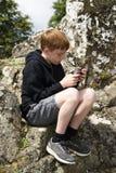 使用他巧妙的电话的十几岁的男孩外面 免版税库存照片