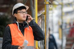 使用他的在建造场所的年轻亚裔工程师智能手机 库存照片