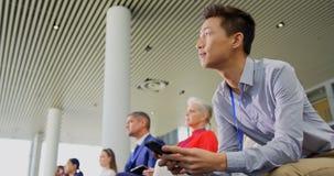 使用他的手机的亚洲商人在企业研讨会4k 影视素材
