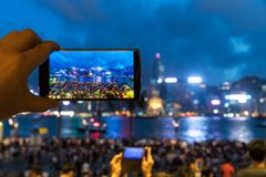 使用他的手机的人拍照片打鸣在沿海岸区 免版税库存照片