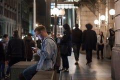 使用他的智能手机在晚上在贝尔格莱德,妇女的年轻白人做同样在背景中 库存图片