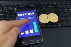 使用他的智能手机的人买bitcoins 有屏幕上bitcoin现金贸易的图的智能手机 10个背景蓝色董事会电路eps模式 Cryptocu 库存图片