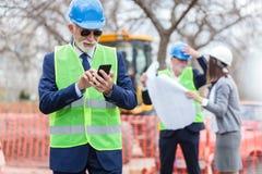 使用他的智能手机的愉快的高级工程师或商人,当检查工地工作时 免版税库存图片