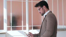 使用他的智能手机的英俊的年轻商人,当坐桌在办公室时 股票视频