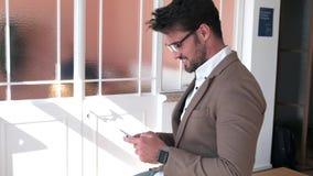 使用他的智能手机的英俊的年轻商人,当坐桌在办公室时 股票录像