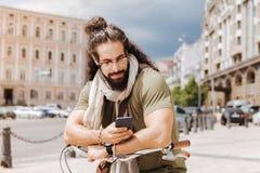 使用他的智能手机的英俊的有胡子的人 免版税图库摄影