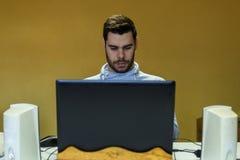 使用他的机动性、片剂、膝上型计算机和耳机的年轻人 免版税库存照片