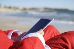 使用他的片剂的圣诞老人项目在海滩 库存图片