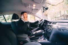 使用他的电话的人,当驾驶汽车时 商人司机讲电话白色推进汽车 免版税库存图片