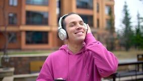 使用他的耳机的年轻人在街道 有智能手机的人走由城市街道的 白种人人年轻人 股票视频