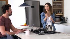 使用他的膝上型计算机和她的女朋友的英俊的年轻人吃酸奶,当在家时站立在厨房 股票视频
