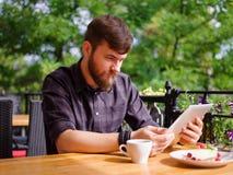 使用他的膝上型计算机的一个年轻有胡子的人在咖啡馆坐 库存照片