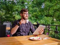 使用他的膝上型计算机的一个年轻有胡子的人在咖啡馆坐 免版税库存图片