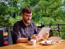 使用他的膝上型计算机的一个年轻有胡子的人在咖啡馆坐 免版税库存照片