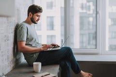 使用他的膝上型计算机的宜人的有胡子的人在家 库存图片