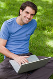 使用他的膝上型计算机的新微笑的人,当盘着腿时坐 库存图片