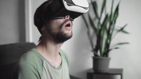 使用他的VR耳机显示的年轻有胡子的行家人为虚拟现实比赛或观看360录影和尝试