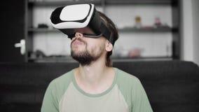 使用他的VR耳机显示的年轻有胡子的行家人为观看360录影,当坐沙发时和吃