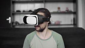 使用他的VR耳机显示的年轻有胡子的行家人开始与虚拟现实的比赛或观看的耳机