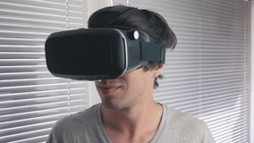 使用他的VR耳机的年轻人为观看360录影在办公室背景 关闭 股票视频