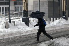 使用伞的人在雪风暴期间 库存照片