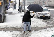 使用伞的人在雪风暴期间 免版税图库摄影