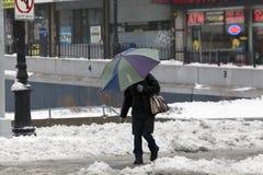 使用伞的人在雪风暴期间 图库摄影