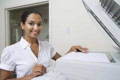 使用传真机的愉快的女实业家在办公室 免版税库存照片
