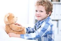 使用作为有听诊器和玩具熊的一位医生的儿童耐心afrer健康检查 图库摄影