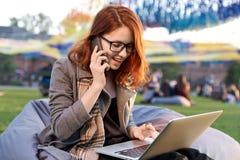 使用便携式的便携式计算机的年轻微笑的女学生为准备对检查在大学,愉快的白种人女性keyb 库存图片