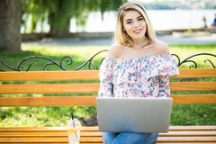 使用便携式的便携式计算机的美丽的年轻白肤金发的女学生,当坐长凳时 年轻美好女孩使用pers 免版税库存照片
