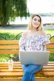 使用便携式的便携式计算机的美丽的年轻白肤金发的女学生,当坐长凳时 年轻美好女孩使用pers 图库摄影