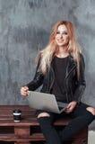 使用便携式的便携式计算机的美丽的年轻女性女孩,当坐在葡萄酒地方时和喝咖啡 免版税库存图片