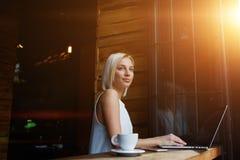 使用便携式的网书的体贴的可爱的女性自由职业者为距离工作 库存照片
