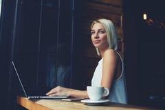 使用便携式的网书的体贴的可爱的女性自由职业者为距离工作 库存图片
