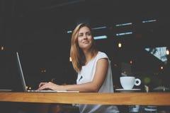 使用便携式的网书的梦想的美丽的女性在工休期间在咖啡店 免版税库存图片